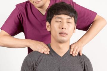 肩こりで来院した男性と施術する柔道整復師